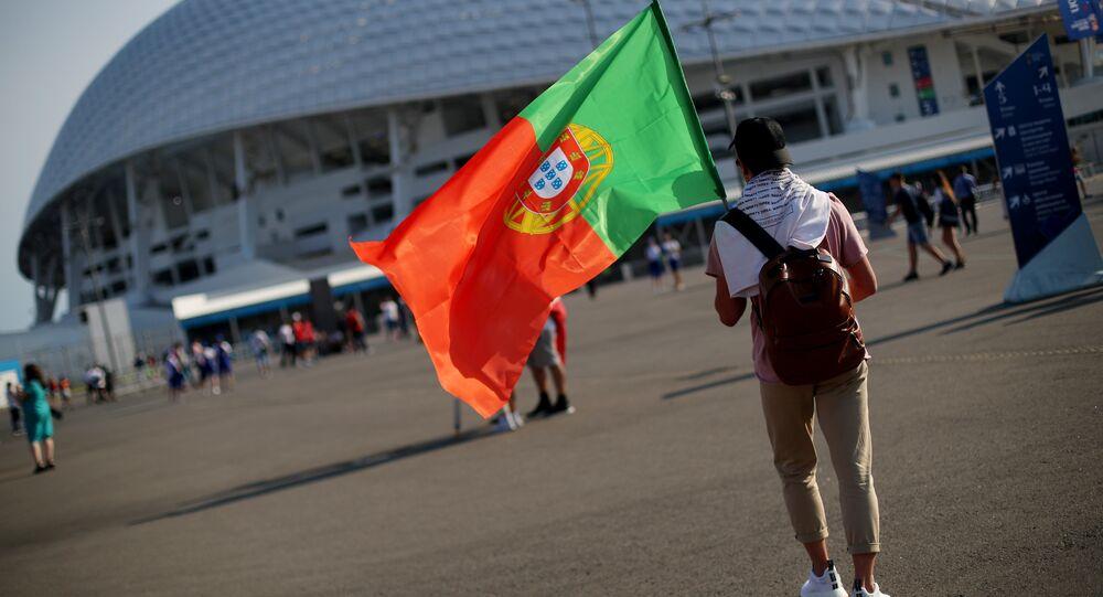 Torcedor português segurando bandeira nacional antes do jogo entre Portugal e Espanha, em Sochi