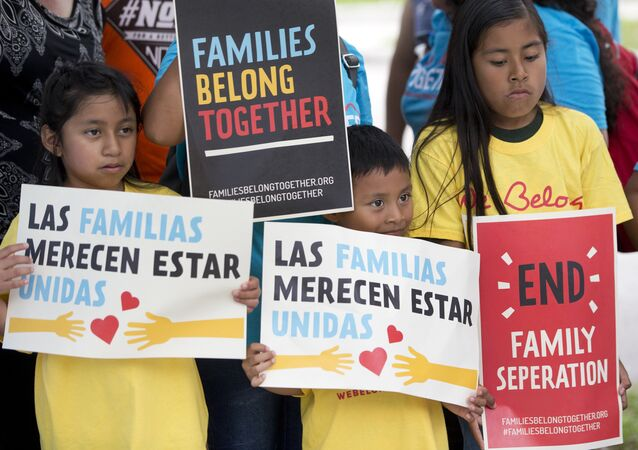 In this June 1, 2018, file photo, children hold signs during a demonstration in front of the Immigration and Customs Enforcement offices in Miramar, Fla. The Trump administration's move to separate immigrant parents from their children on the U.S.-Mexico border has turned into a full-blown crisis in recent weeks