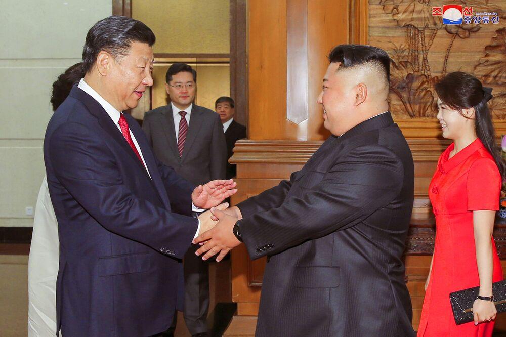 Os líderes da China, Xi Jinping, e da Coreia do Norte, Kim Jong-un, apertam as mãos durante seu encontro em Pequim em 19 de junho de 2018