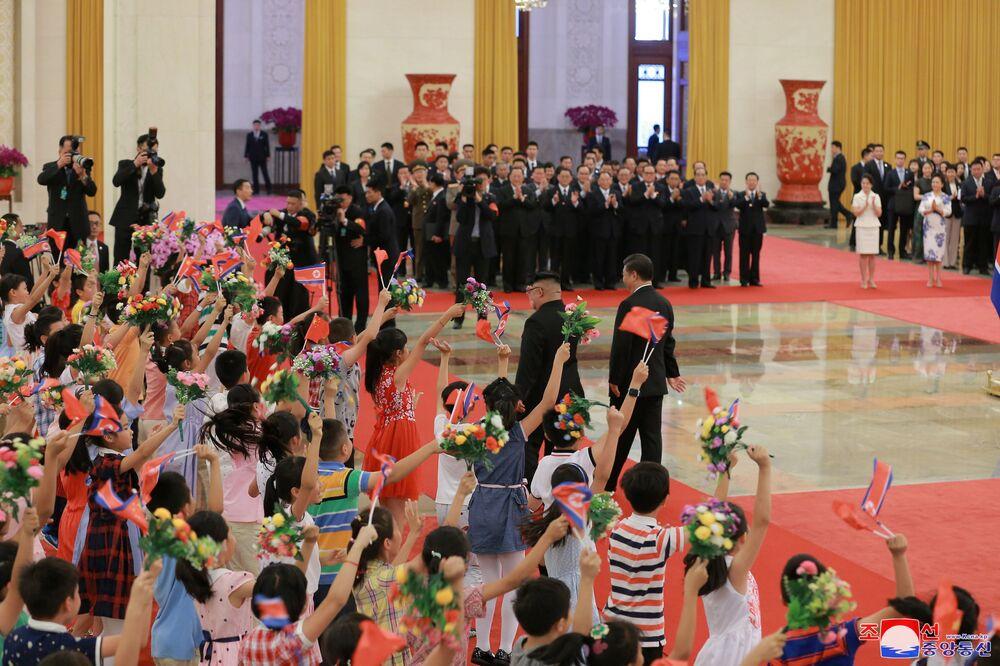 Crianças oferecem flores, cumprimentando os líderes chinês e norte-coreano em Pequim