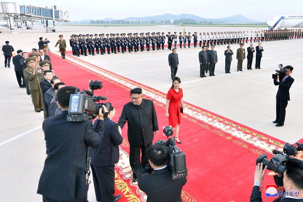 O líder da Coreia do Norte, Kim Jong-un, e sua esposa, Ri Sol-ju, caminham no tapete vermelho em Pequim no âmbito da visita oficial