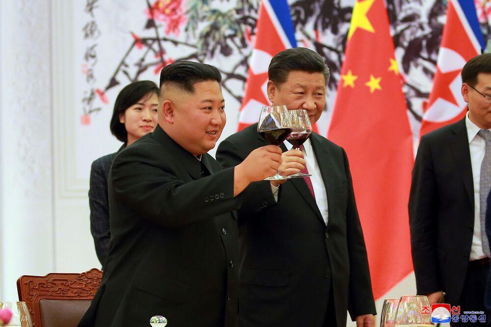 O presidente da China, Xi Jinping, e o líder da Coreia do Norte, Kim Jong-un, levantam taças durante o encontro oficial em Pequim