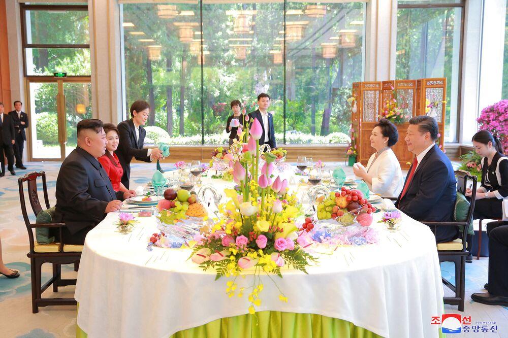 Os líderes da China, Xi Jinping, e da Coreia do Norte, Kim Jong-un, assistem ao almoço conjunto, acompanhados por suas esposas, durante o encontro em Pequim