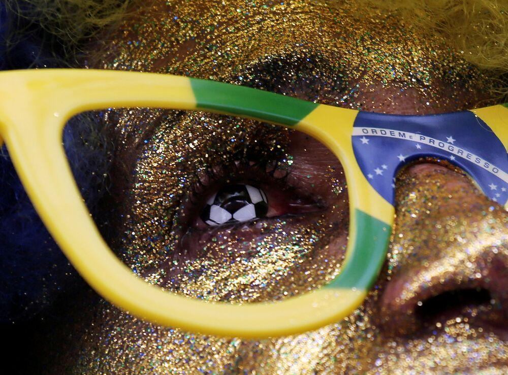 Torcedor brasileiro, em São Paulo, assiste ao jogo Brasil x Costa Rica, pela Copa do Mundo. Ele usa uma lente em formato de bola de futebol.