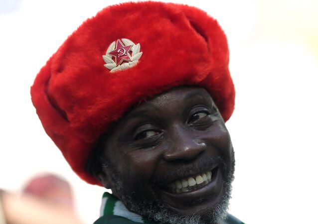 Torcedor nigeriano sorri com um gorro soviético enquanto assiste a seleção da Nigéria vencer a Islândia por 2x0 em Volgogrado durante a Copa do Mundo.