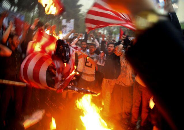 Manifestantes iranianos queimam representações da bandeira dos EUA durante um protesto em frente à ex-embaixada dos Estados Unidos em resposta à decisão do presidente Donald Trump de desistir do acordo nuclear e renovar as sanções a Teerã.