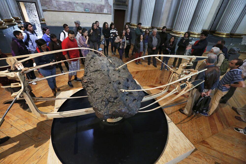 Pessoas observando o meteorito La Concepcion no Museu Ex Teresa Arte Actual, na Cidade do México