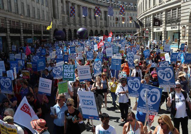 Em Londres, manifestantes seguram placas e faixas durante marcha em apoio ao NHS, o serciço nacional de saúde britânico.