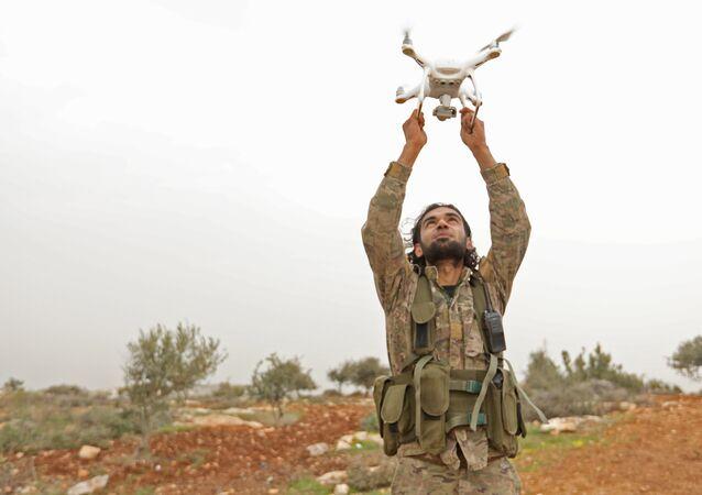 Rebelde sírio apoiado pela Turquia usando um drone em um posto de monitoramento perto da cidade síria de Qilah