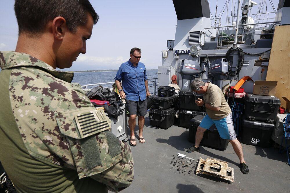 Funcionário da DPAA tirando fotos de fragmentos do avião norte-americano P-47 Thunderbolt a bordo do navio francês FS Pluton M622