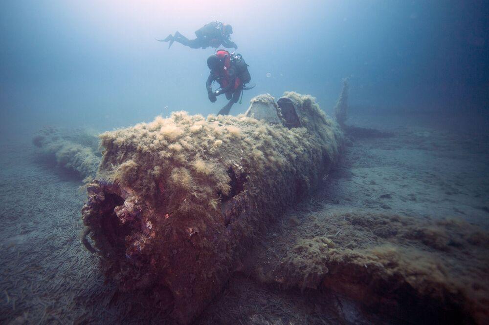Mergulhadores militares franceses nadando sobre destroços do avião norte-americano P-47 Thunderbolt, perto da ilha de Córsega