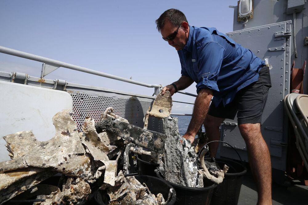 Funcionário da DPAA analisando destroços do avião norte-americano P-47 Thunderbolt a bordo do navio francês FS Pluton M622