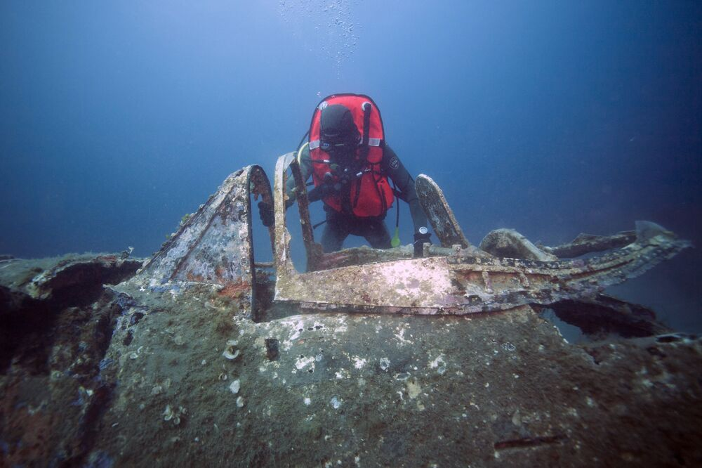 Mergulhador militar francês olhando para os destroços do avião norte-americano P-47 Thunderbolt, perto da ilha de Córsega