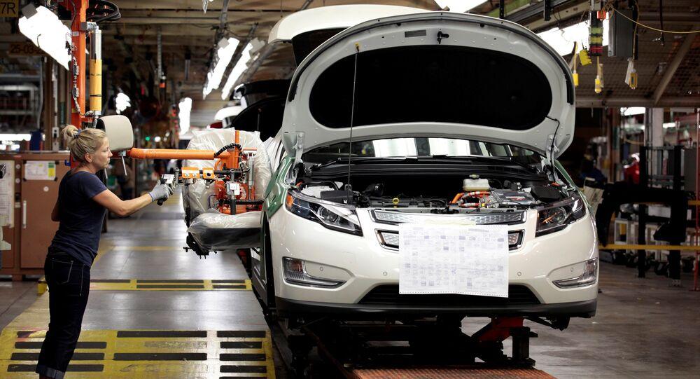 Membro do sindicato da United Auto Workers, Carrie Attwood, usa um braço ergonômico para instalar um banco dianteiro em um veículo elétrico Chevrolet Volt na fábrica da General Motors.