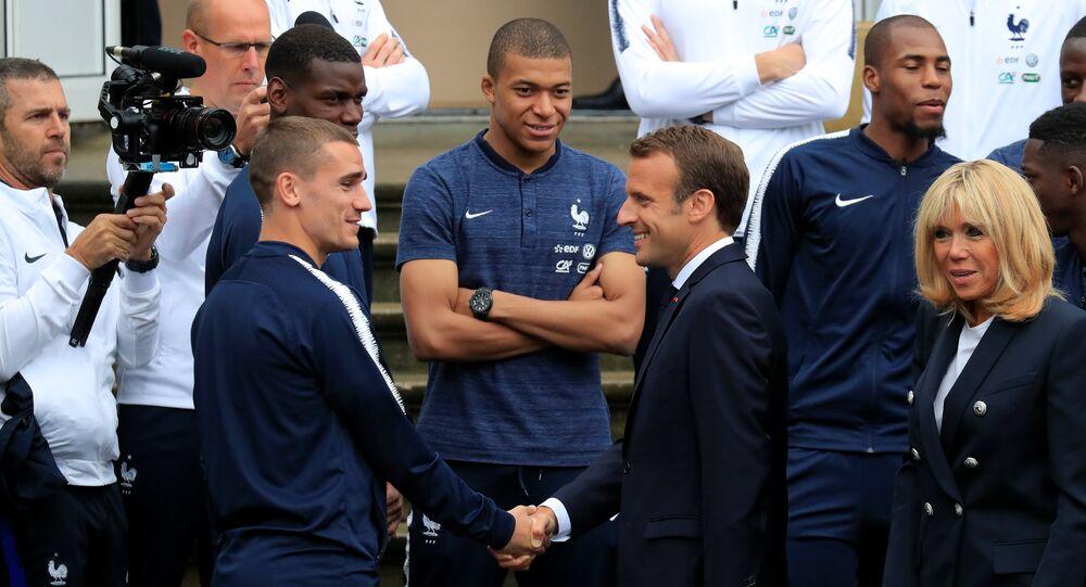 O presidente francês, Emmanuel Macron, aperta a mão do jogador da seleção francesa, Antoine Griezmann,