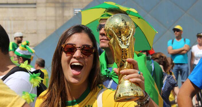 Torcedora brasileira levanta réplica da taça ao dar boas-vindas à Seleção perto do hotel Mirage, em Kazan, em 5 de julho de 2018