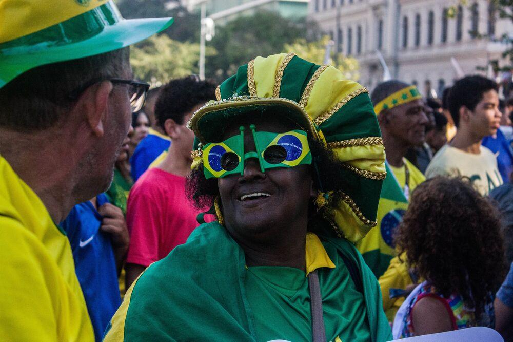 Torcedora sorri trajada dos pés à cabeça com as cores do Brasil.
