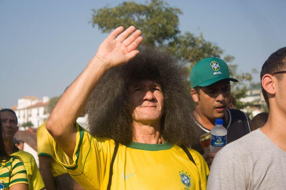 Torcedor tenta tapar o sol para assistir ao jogo do Brasil contra a Bélgica na Copa do Mundo de 2018.