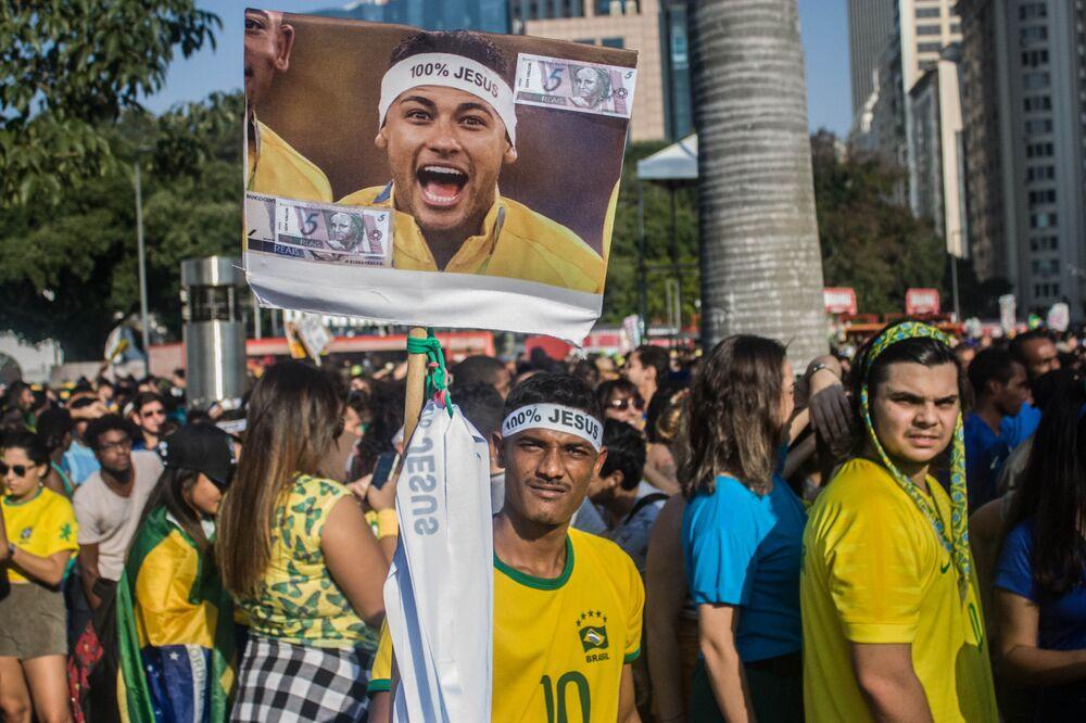 Vendedor de faixas 100% Jesus carrega placa com o rosto de Neymar.