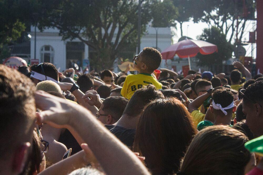 Menino olha para esquerda nos ombros de um adulto em meio à multidão que tomou o Centro do Rio de Janeiro para acompanhar os jogos do Brasil na Copa do Mundo de 2018.