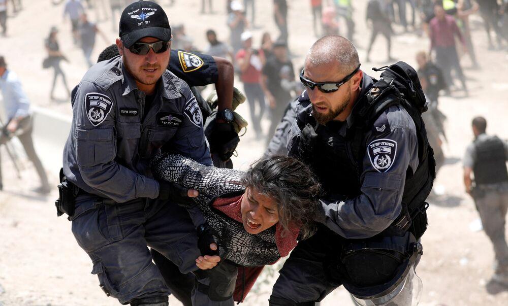 Policiais israelenses detendo uma moça palestina na região da Cisjordânia