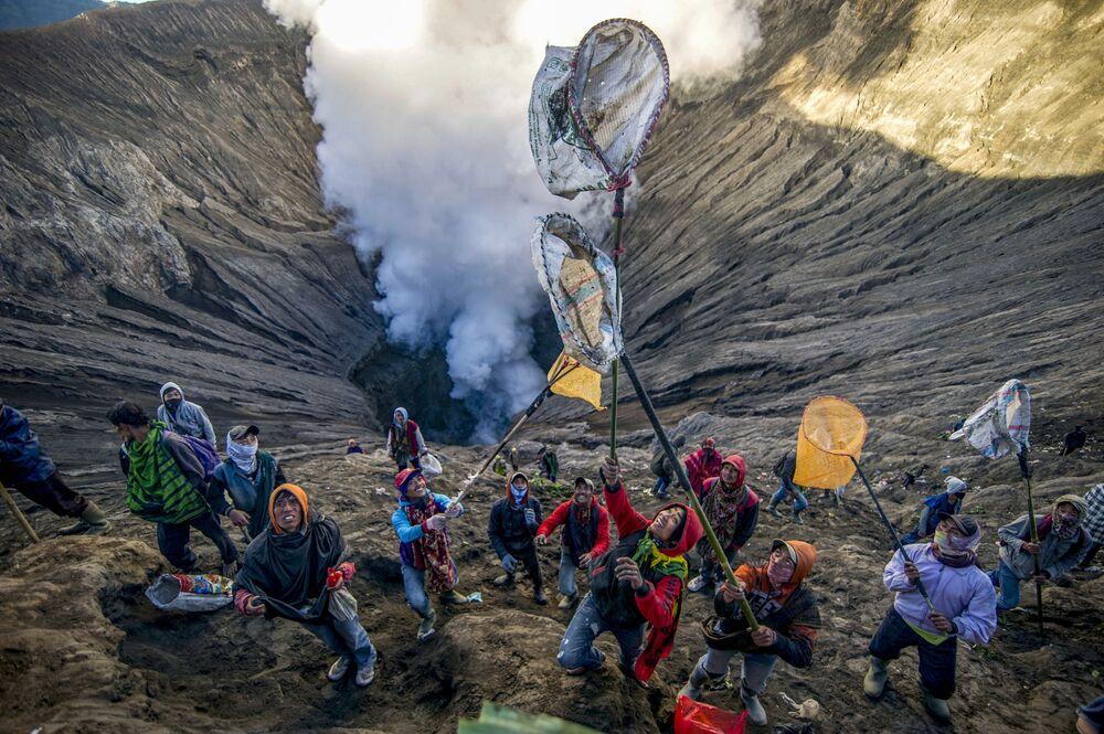 Pessoas se preparando para pegar oferendas atiradas por representantes da tribo Tengger no vulcão ativo Mount Bromo para celebrar o Festival Hindu Yadnya