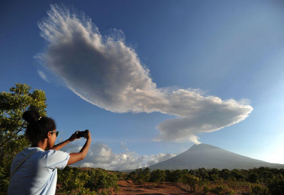 Mulher fotografando fumaça de vulcão na ilha indonésia de Bali