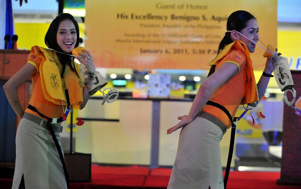 Aeromoças da empresa aérea filipina Cebu Pacific, dançando durante uma demonstração de segurança na área de desembarque do aeroporto de Manila