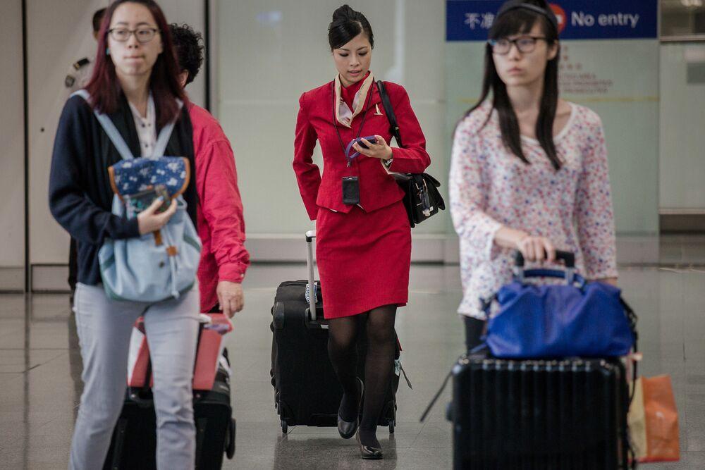 Aeromoça da companhia aérea de Cathay Pacific com sede em Hong Kong carregando sua bagagem