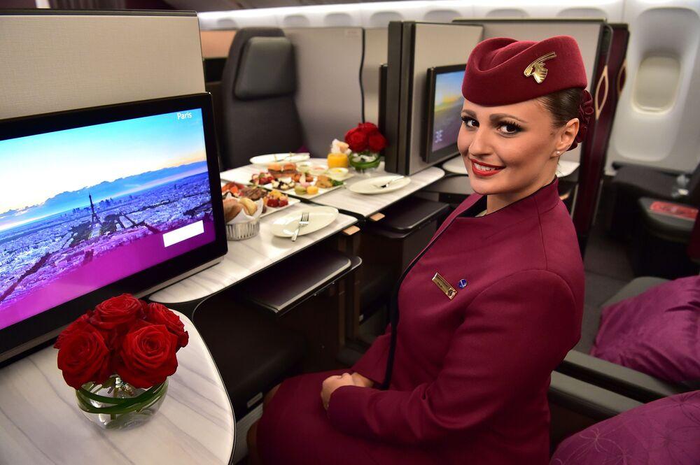 Aeromoça da empresa aérea Qatar Airways a bordo da primeira classe do Boeing 777 no salão aéreo internacional no aeroporto de Le Bourget