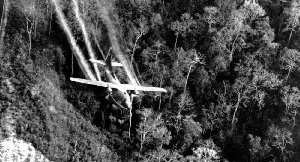 Avião C-123 da Força Aérea dos EUA voando baixo sobre rodovia no Vietnã do Sul e dissipando substâncias químicas sobre a selva