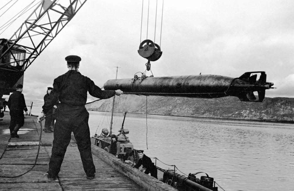 Marinheiros da Frota do Norte da Marinha da Rússia transportam torpedos em lanchas.