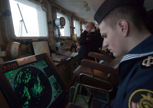 Um membro da tripulação de um navio acompanha os indicadores do radar