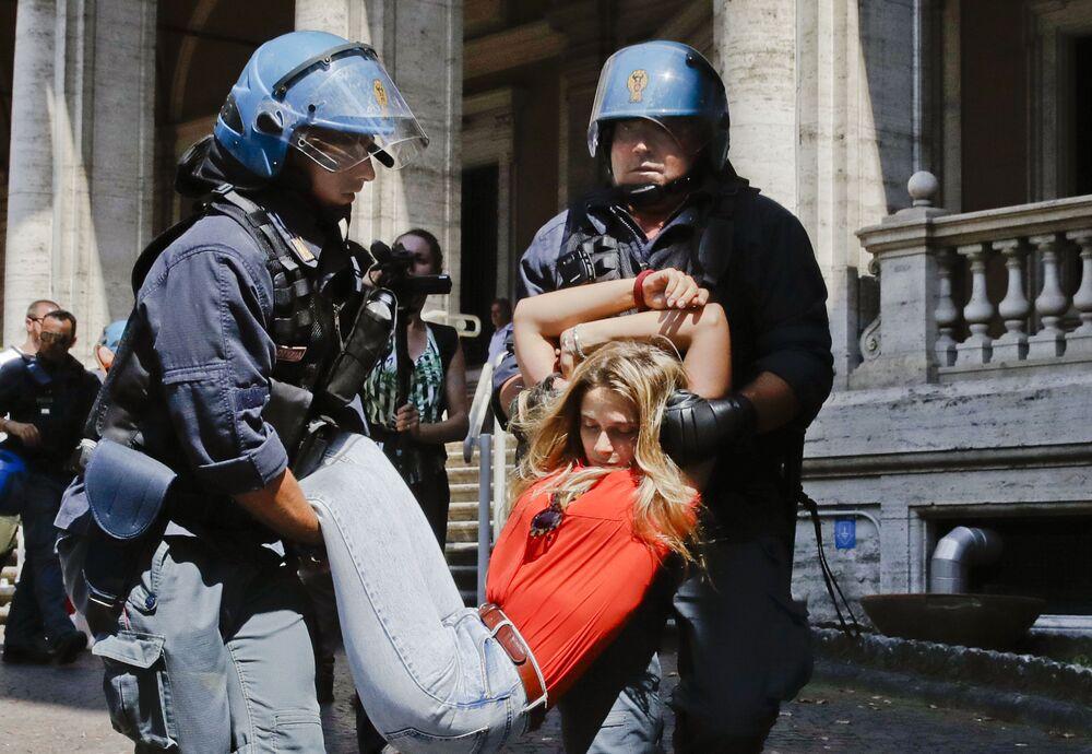 Policiais arrastam uma manifestante perto do edifício do Ministério de Transportes em Roma, na Itália