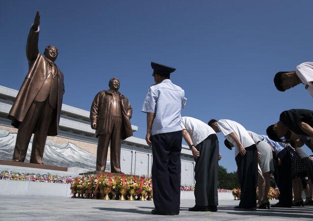 Cidadãos norte-coreanos prestam homenagem às estátuas dos líderes Kim Il-sung e Kim Jong-il em Pyongyang