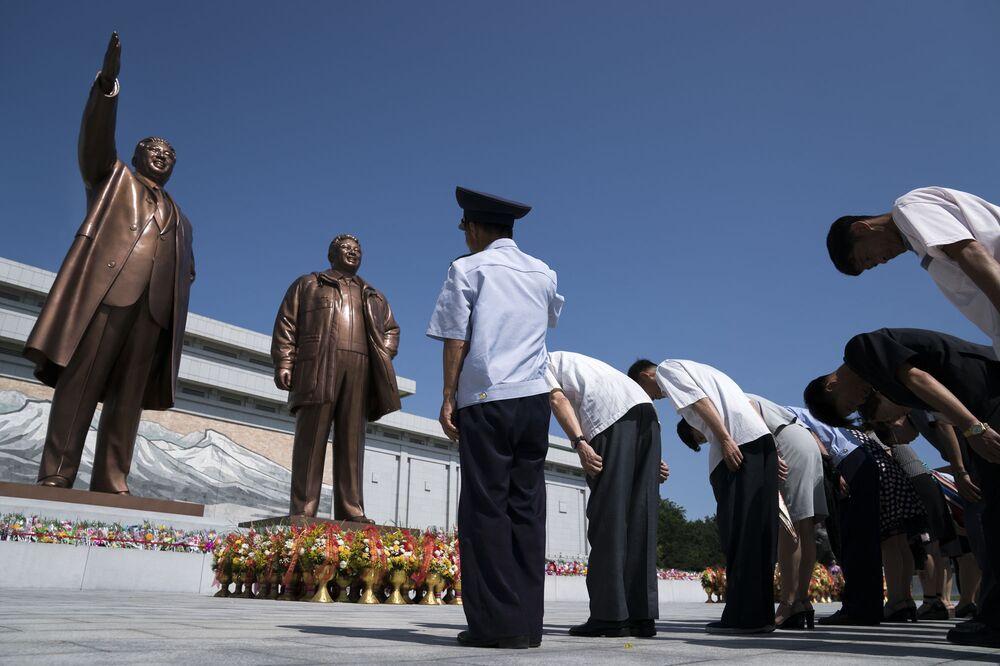 Cidadãos norte-coreanos prestam homenagem às estátuas dos líderes Kim Il-sung e Kim Jong-il, em Pyongyang
