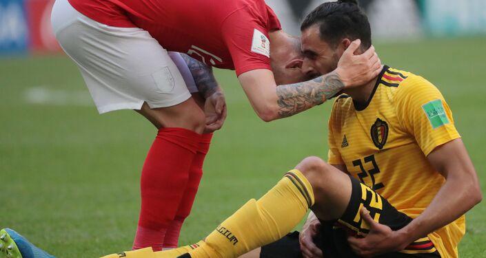 O inglês Kieran Trippier ajuda o belga Nacer Chadli, caído no chão.