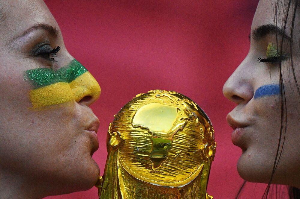 Torcedoras brasileiras com réplica da taça na partida das quartas de final da Copa 2018 entre o Brasil e a Bélgica