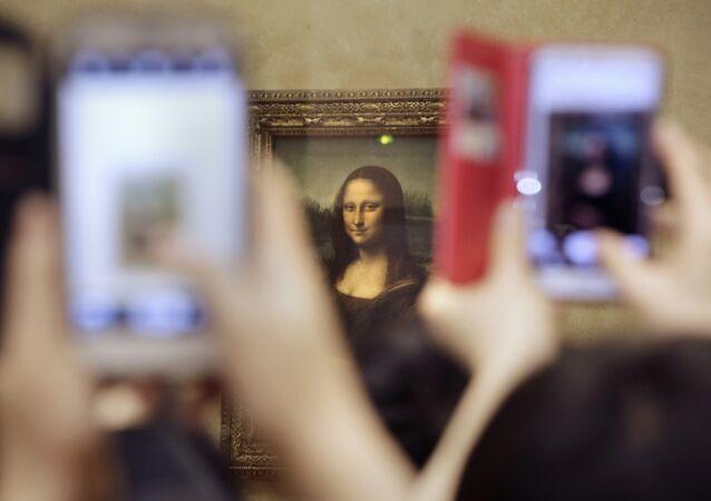Turistas tiram fotos para a pintura de Leonard de Vinci, Mona Lisa, no Museu do Louvre, em Paris, França.