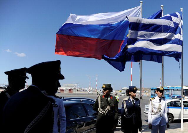 Polícia grega e oficiais do exército perto das bandeiras russas e gregas no aeroporto de Atenas, aguardando pela chegada do presidente russo, Vladimir Putin.