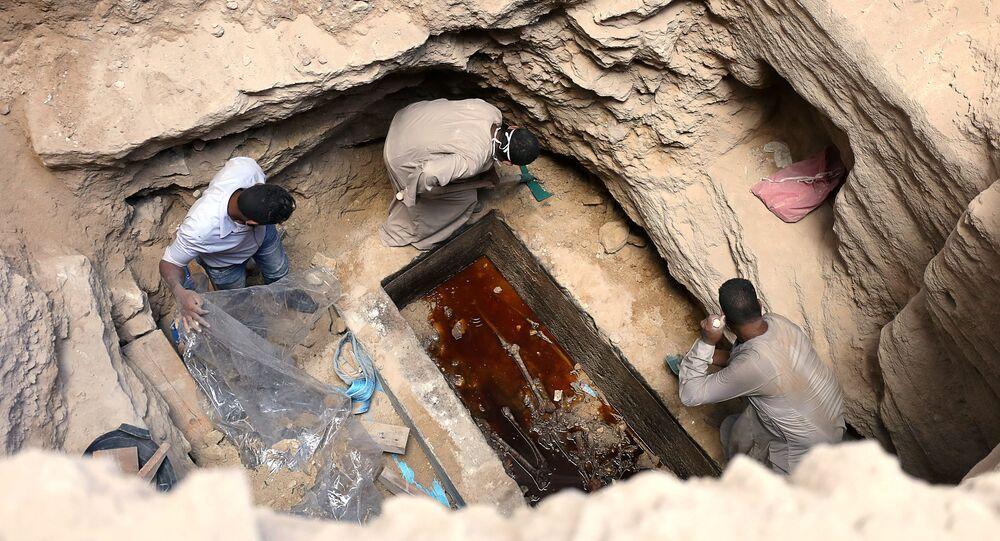 Arqueólogos desenterrando um sarcófago com três múmias em Alexandria, Egito, 19 de julho de 2018