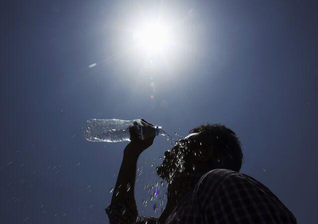 Homem derrama água no rosto durante um dia quente de verão em Hyderabad, Índia.