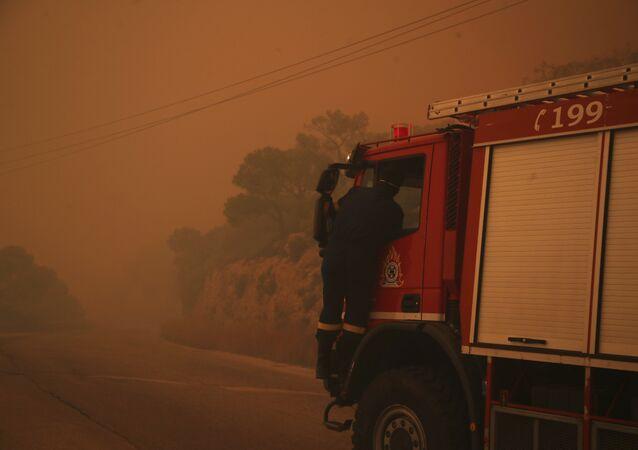 Caminhão de bombeiros envolto em um manto de fumaça laranja em uma estrada perto de Kineta, a oeste de Atenas, segunda-feira, 23 de julho de 2018.