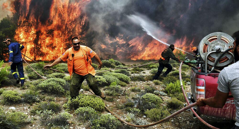 Bombeiros e voluntários tentando extinguir o fogo durante os incêndios florestais nos subúrbios de Atenas, Grécia