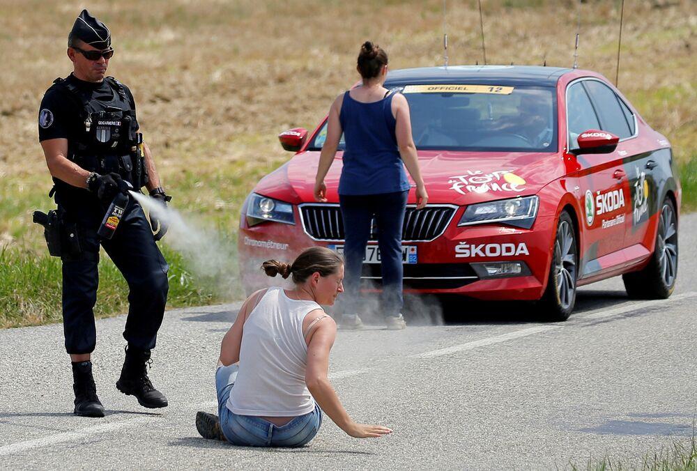 Policial usa spray de pimenta contra uma manifestante durante a competição Volta à França em bicicleta.
