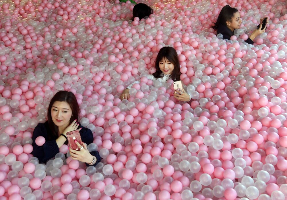 Visitantes do museu Sugar Republic (República do Açúcar) tirando selfies no meio de bolas parecidas com doces, em Melbourne, Austrália.