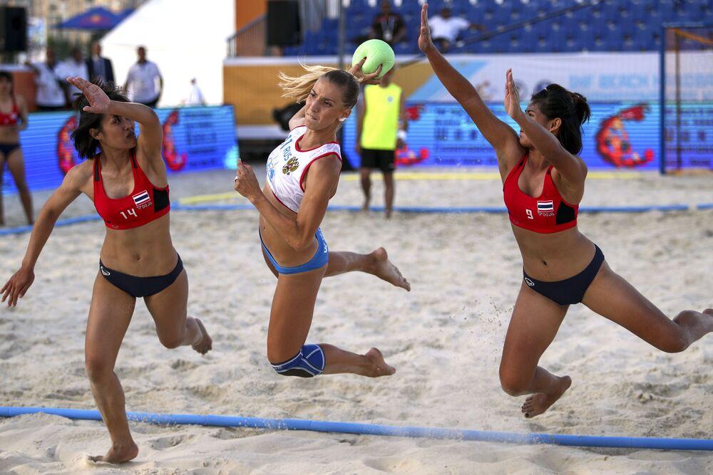 Jogadoras tailandesas tentam tirar a bola das mãos da esportista russa na partida de handebol de praia feminino