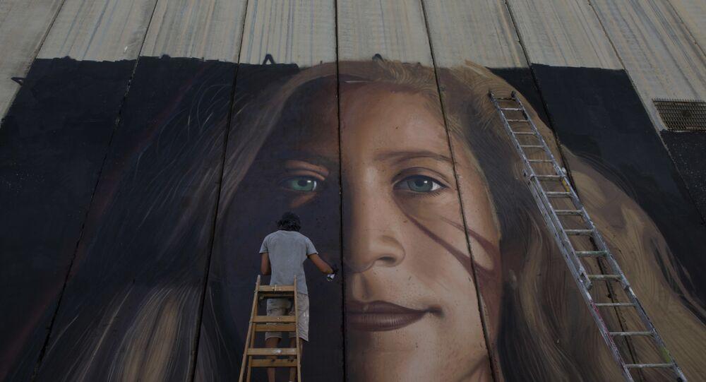 Um artista pinta um mural gigante da ativista palestina Ahed Tamimi em parte da barreira de separação israelense, na Cisjordânia.
