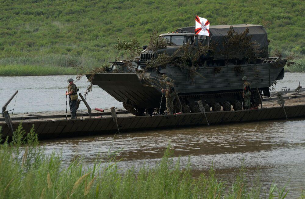 Veículo de transporte anfíbio é visto atravessando a ponte no decurso da tarefa em que deve atravessar o rio