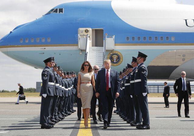 O presidente dos EUA, Donald Trump, e a primeira-dama Melania Trump, caminham no tapete em frente ao Força Aérea Um após descer em Londres.